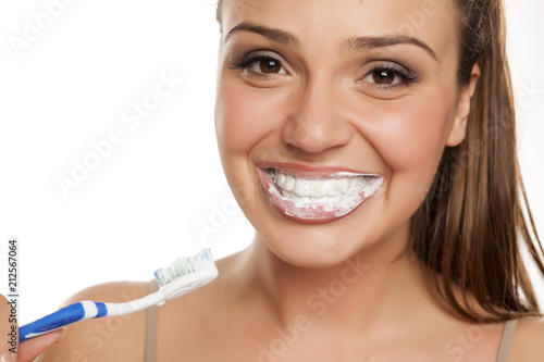 Leinwanddruck Bild young happy woman brushing her teeth on white background