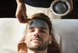 Leinwanddruck Bild - Man getting a mud mask at a spa