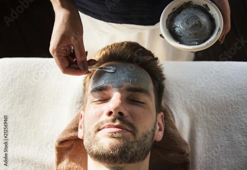 Leinwanddruck Bild Man getting a mud mask at a spa