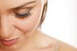 close up of female eye with false eyelashes on white background