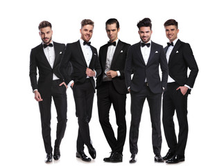 five handsome men in black tuxedoes standing together