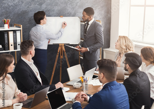 Wall mural Woman and man giving presentation to colleagues in office