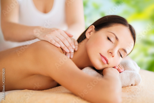 Fotobehang Spa wellness, spa and beauty concept - close up of beautiful woman having massage over green natural background