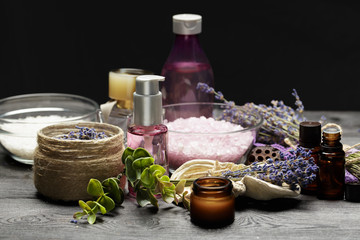 Aromatic composition of lavender, herbs, cosmetics and salt on a dark table top