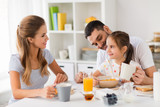 family, eating and people concept - happy mother, father and daughter having breakfast at home - 212584469