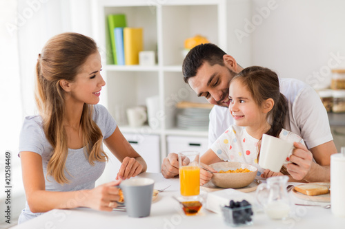 Wall mural family, eating and people concept - happy mother, father and daughter having breakfast at home