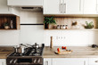 Cooking on Modern Kitchen  in scandinavian style. stylish kitchen interior with modern furniture and stainless steel appliances. wooden countertop, steel stove, board,knife and spices, tomatoes - 212587091