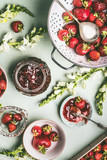Fresh strawberries in colander and bowls with jam jar and spoon on kitchen table background with garden flowers, top view. Summer berries preserve concept. Seasonal local organic food - 212588698
