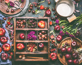 Wooden box with selection of summer fruits and berries: strawberries, peaches, plums, cherries, gooseberries and currants on rustic background with cooking pot and spoon, top view, flat lay. - 212588886