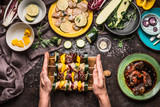 Female hands holding various homemade meat vegetables skewers for grill or bbq on rustic background with ingredients , plates and kitchen tools, top view, flat lay. Food, eating and cooking concept - 212589288