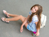 girl with long hair sitting on skating board - 212591013