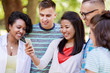 friendship, technology and international concept - group of happy smiling with smartphone outdoors