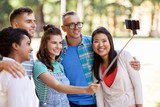people, friendship and international concept - happy smiling young woman and group of happy friends taking picture by selfie stick in park - 212593073