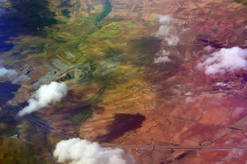 Dramatic aerial view from plane of  patchwork farmland and houses © hibrida
