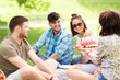 friendship, leisure and summer concept - group of happy friends eating watermelon at picnic in park