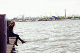 Young adult woman sitting on a wooden jetty on the river - 212597435