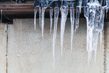 Icicles hang on old house roof - 212599428
