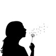 Silhouette of a little girl blowing dandelion