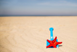 beach with kid toys shovel, bucket and red sea star