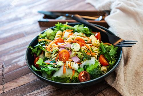Salad with fusilli pasta accompanied tomatoes, mozzarella, smoked ham and italian cheese - 212601651