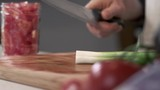 Chef slicing fresh green onion with kitchen knife - 212603001