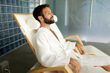 Handsome man relaxing in chair at spa center © nd3000