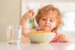 Leinwanddruck Bild - Beautiful blond child eating spaghetti with fork at home