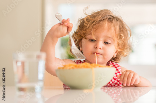 Beautiful blond child eating spaghetti with fork at home - 212608452