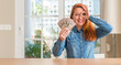 Redhead woman holding dollar bank notes at home with happy face smiling doing ok sign with hand on eye looking through fingers