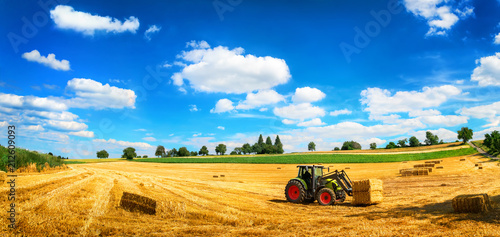 Poster Sommer am Land: Traktor beim Laden von Stroh