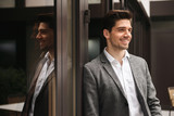 Smiling young businessman standing at the glass doors