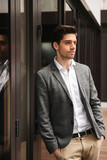 Serious young businessman standing at the glass doors