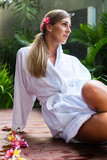Woman with blossoms wearing bath robe at wellness spa pool