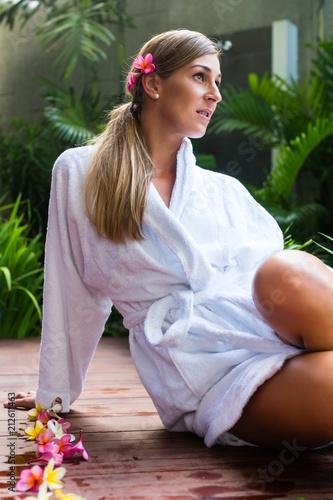 Kobieta z kwiatami na sobie szlafrok na basen spa wellness