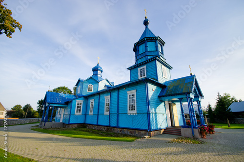 Leinwanddruck Bild Blue wooden church in Narew, Poland