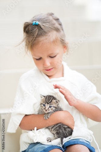 Fototapeta little girl plays for four years with a kitten