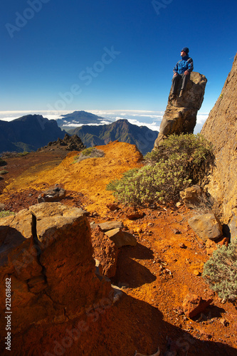 Fotobehang Nachtblauw Resting man sitting on the rock above the crater Caldera de Taburiente, Island of La Palma, Canary Islands, Spain