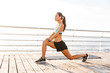 Leinwanddruck Bild - Profile photo of brunette fitness woman 20s in tracksuit doing lunges, and stretching legs on boardwalk near seaside