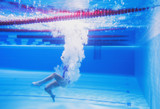 beautiful young girl with a good figure swims under water, effectively dives