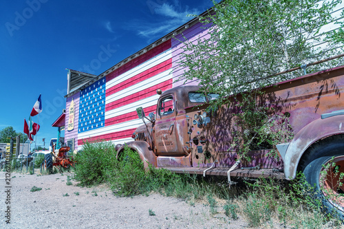 Aluminium Route 66 SELIGMAN, AZ - JUNE 29, 2018: Old truck and american flag along Route 66. This is the most famous historic route in the US
