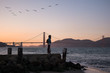 woman looking at golden gate in san francisco at sunset with birds in a pattern