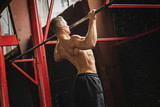Strong man doing pull up exercise in the gym - 212626817