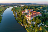 Tyniec near Krakow, Poland. Benedictine abbey, monastery and church on the rocky cliff and Vistula river. Aerial view at sunset. Bielany monastery far in the background