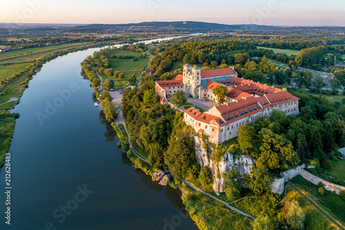 Leinwanddruck Bild Tyniec near Krakow, Poland. Benedictine abbey, monastery and church on the rocky cliff and Vistula river. Aerial view at sunset. Bielany monastery far in the background