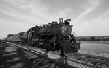 Steam train on tracks coming at you in black and white