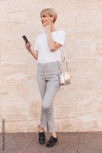 Pełnej długości obraz stylowy blond kobieta 30s sobie biały t-shirt za pomocą telefonu komórkowego, stojąc przed beżowym ścianie odkryty i dotykając słuchawki bluetooth