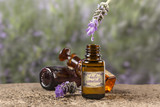 Lavender essential oil drop Oil from a Lavender flower dropping to a bottle. (with a french label) - 212636201