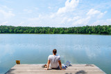 man sitting with laptop and looking on lake. working at vacation. summer time concept - 212636826