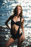 Sexy girl model in swimsuit posing on sea background - 212639077