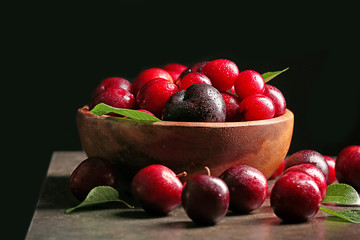 Bowl with ripe juicy plums on dark background